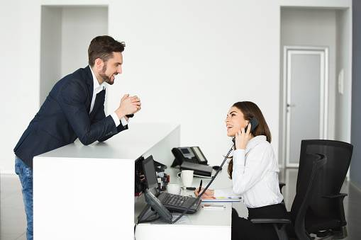 Smiling businessman and female receptionist communicating.